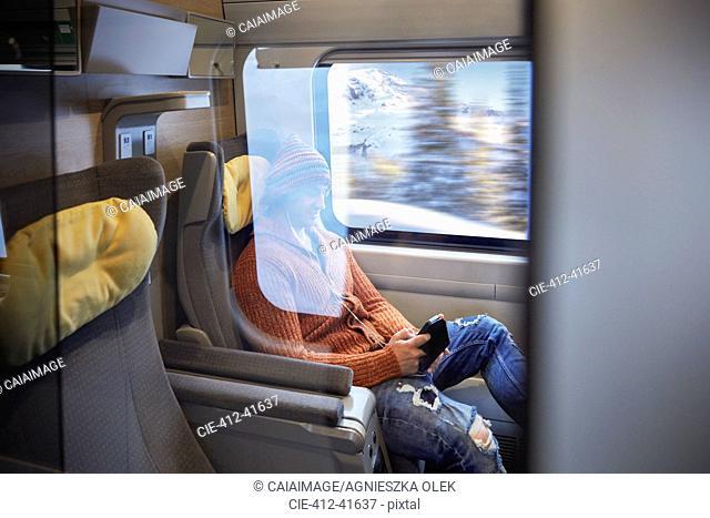 Young man using smart phone on passenger train