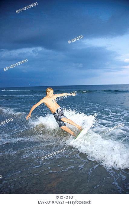 Caucasian male teen riding skimboard