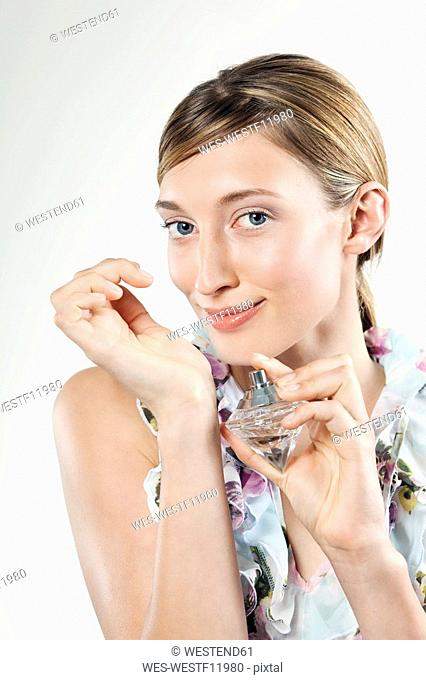 Young woman applying perfume to wrist, portrait