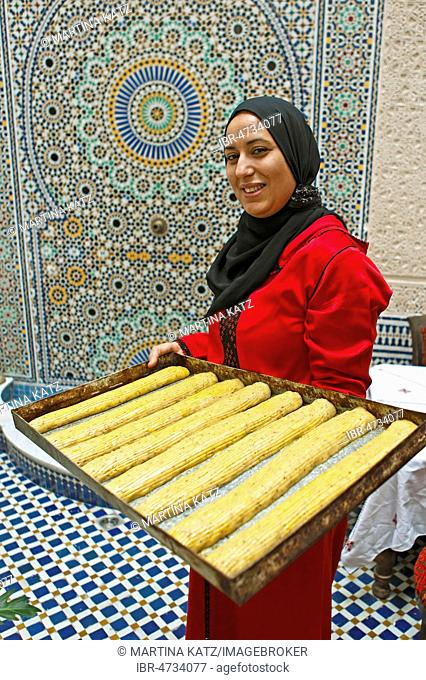 Woman, 30 years, holding a tin with fekkas, cookies, for baking, Fès, province Fès-Meknès, Morocco