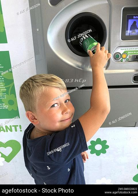 Little blond boy, seven years old, recycling cans and earn pocket money in Ystad, Scania, Sweden, Scandinavia