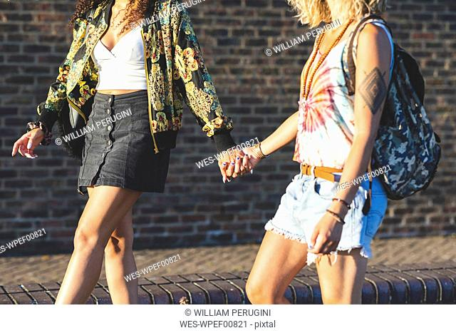 Two young women holding hands walking along brick wall