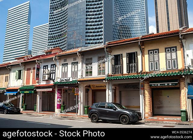 Singapore, Republic of Singapore, Asia - Old buildings built in the style of traditional shophouses are towered by modern high-rise buildings in the Muslim...