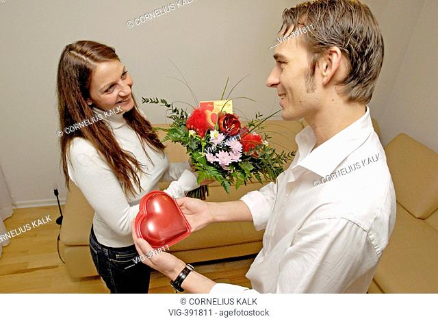 A man presents his wife a chocolate heart and a bouquet of flowers to the valentine's day  - Hamburg, GERMANY, 04/02/2007