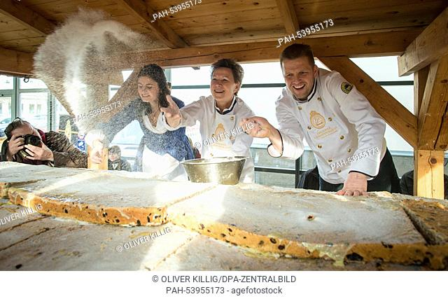 Dresden's Lord Mayor Helma Orosz (2-R), Dresden Stollen Girl Luise Fischer (L)and baker ReneKrause (R) cover the giant stollen with sugar in the Neue Messe...