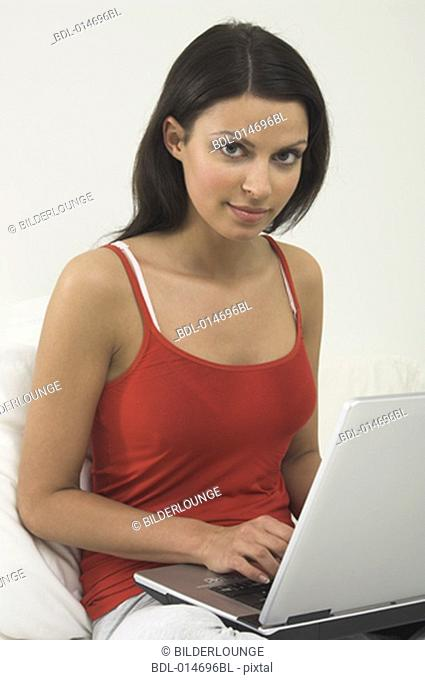 young woman with laptop computer looking at camera