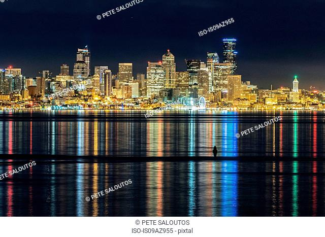 Skyline and city lights reflected in Puget Sound at night, Seattle, Washington, USA