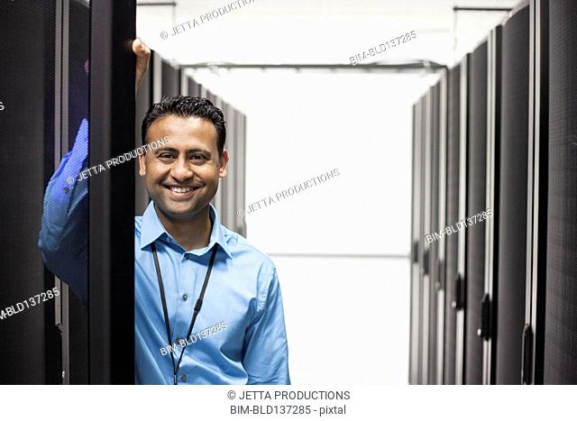 Indian businessman smiling in server room