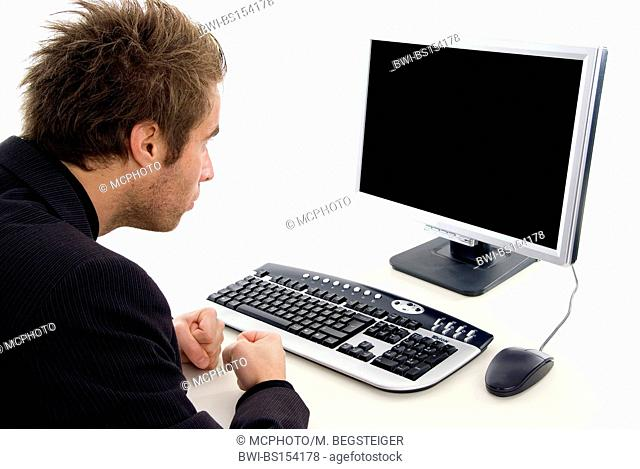 man sitting at a desk in front of a black screen