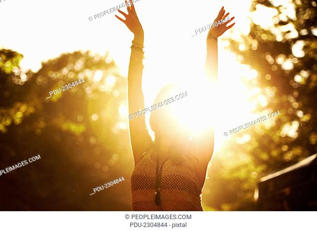 Backlight shot of a young woman enjoying herself at an outdoor festival