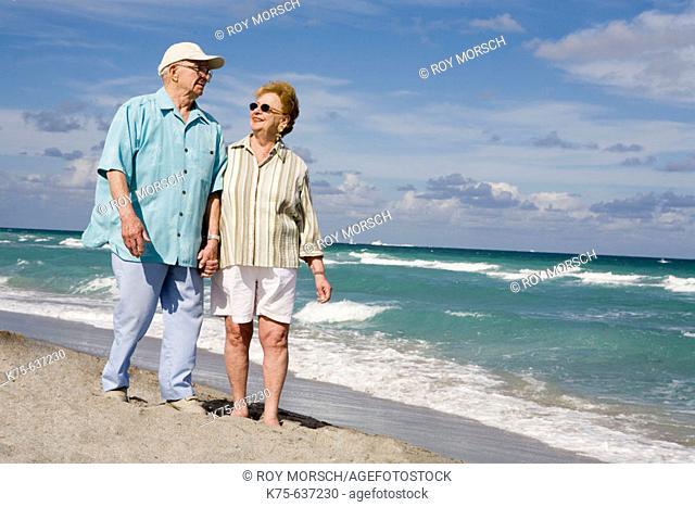 Senior couple walking hand in hand on beach