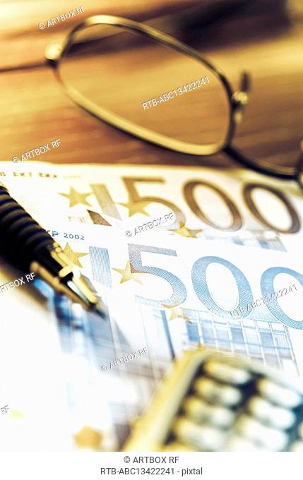 Close-up of five hundred Euro banknotes with pen and eyeglasses