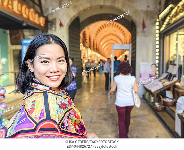 Beautiful woman poses in front of Gate of Egypt Bazaar in Eminonu,Istanbul,Turkey