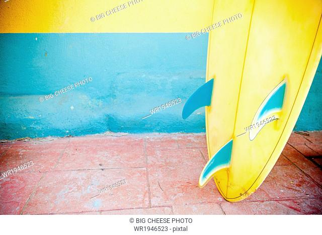 Close up of a yellow, tri-fin, vintage surfboard