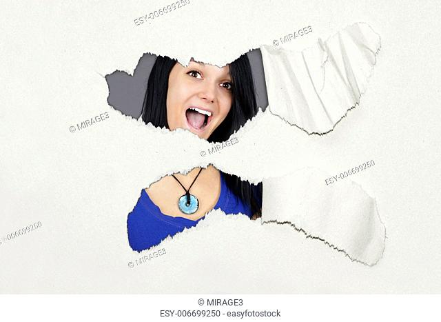 Very surprised young woman under ripped thick textured paper, fun advertisement