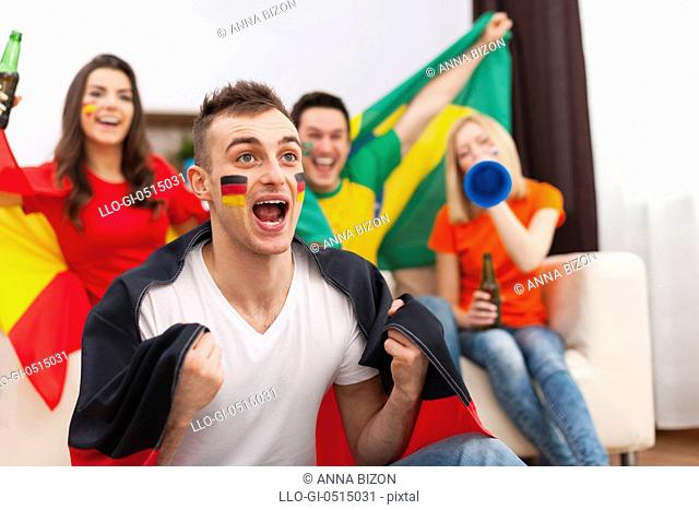 Excited german man with her friends cheering football match. Debica, Poland