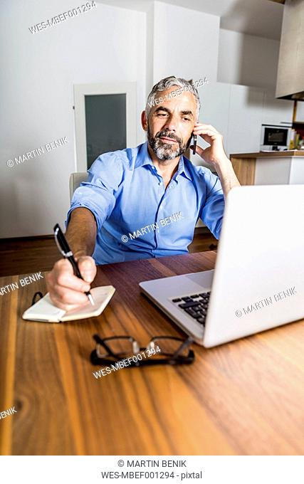 Portrait of businessman telephoning with his smartphone while making notes