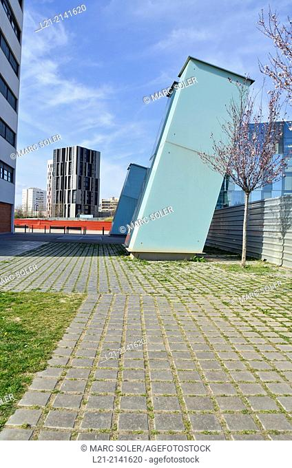 Green grass, red aluminium wall, buildings, blue sky. Plaça Europa, Plaza Europa, District VII, Gran Via, Hospitalet de Llobregat, Barcelona province, Catalonia