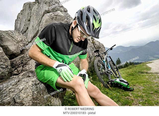 Young man with injured leg sitting on rock with bicycle, Bavaria, Germany