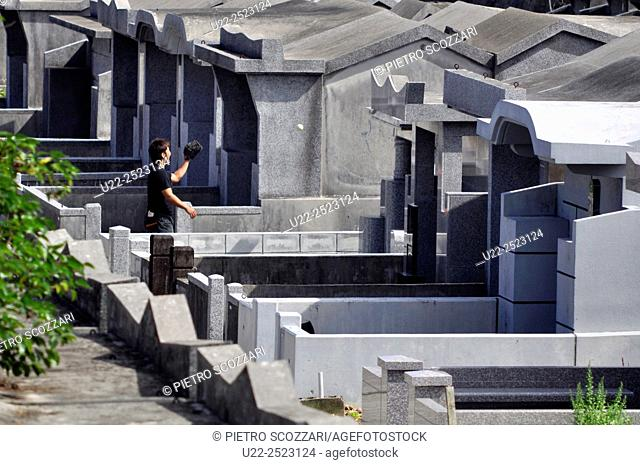 Naha, Okinawa, Japan: a young man playing baseball between the tombs of Shikinaen cemetery during Shimi period, when families gather by the tombs of their...