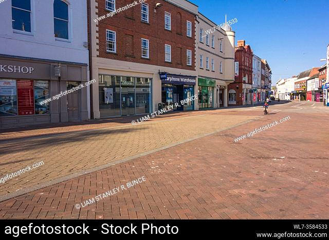 A child cycling along a deserted Street during the Covid-19 lockdown Hereford Herefordshire UK. April 2020