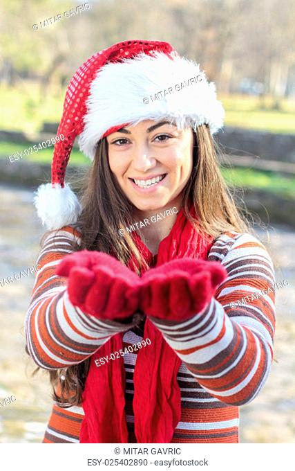 Happy Christmas Young Woman with Santa hat outdoor