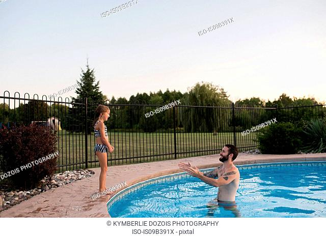 Young girl standing on edge of swimming pool, father in pool encouraging her to jump in