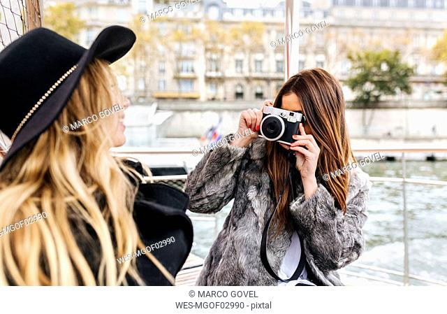 France, Paris, tourist taking picture of her friend with camera