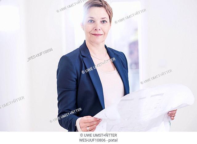 Portrait of confident real estate agent holding plan