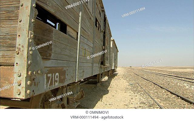 Wooden train wagons on desert with railway tracks