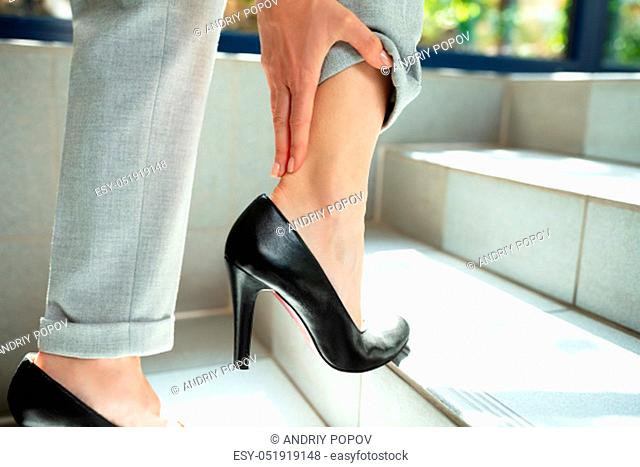 Close-up Of Businesswoman Standing On Staircase Removing High Heels Touching Her Paining Ankle
