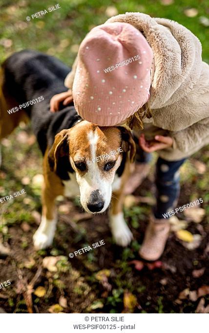 Little girl kissing dog in autumnal garden