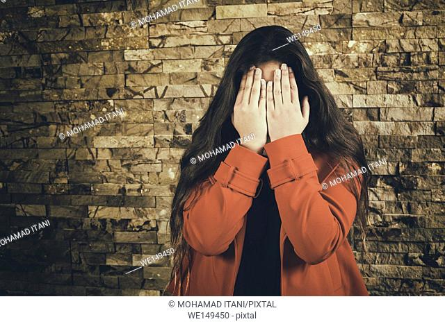 Scared teenage girl hiding face with hands crying