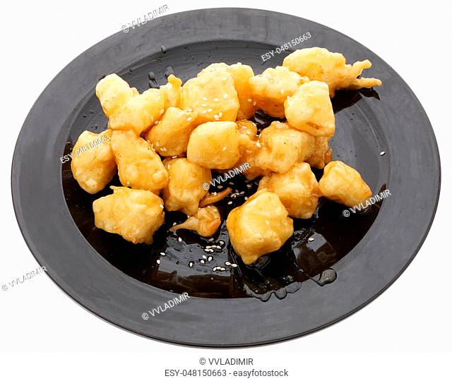 Chinese food. Caramelized apples in black plate isolated on white. Closeup