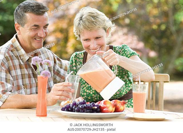 Mature couple sitting at a breakfast table and smiling