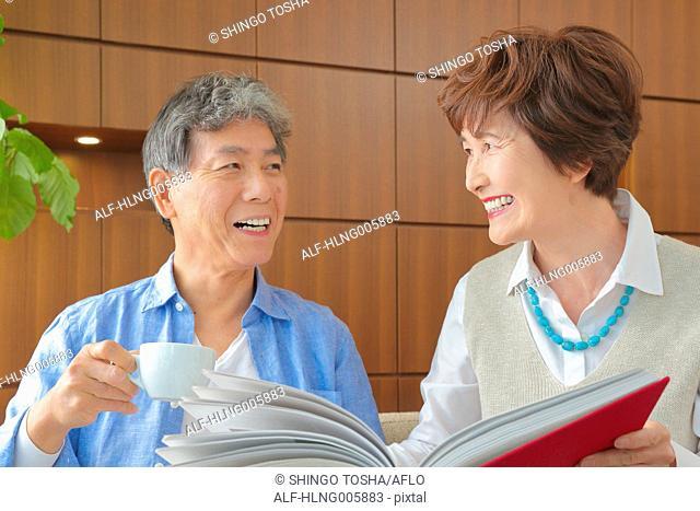 Fashionable Japanese senior couple on sofa