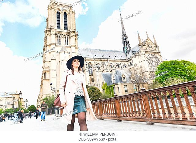 Stylish young woman strolling at Notre Dame, Paris, France