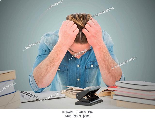 Stressed man at desk against light blue background
