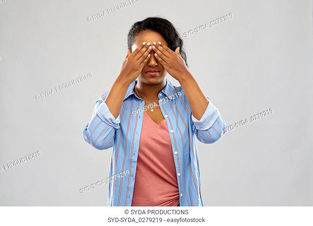 african american woman with eyes closed by hands
