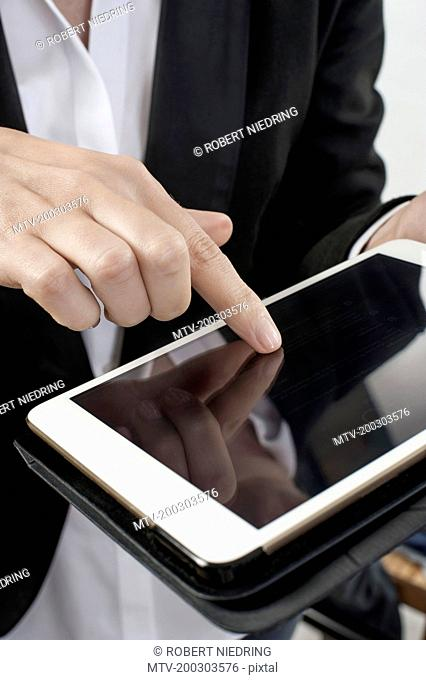 Mid section view of businesswoman operating digital tablet in office, Bavaria, Germany