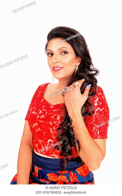 A lovely young woman in a red blouse and with long curly black hair.standing waist up isolated for white background.