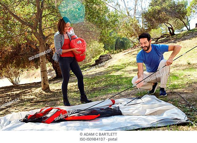 Mid adult couple camping, erecting their tent