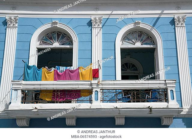 Laundry drying on a balcony of a blue house in colonial style, Santiago de Cuba