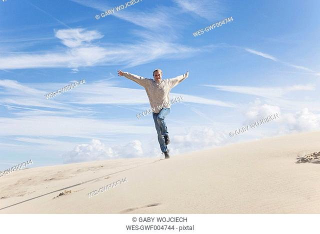 Enthusiastic mature woman running along sand dune