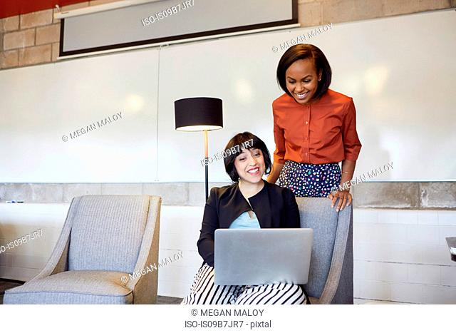 Mid adult woman sitting in chair, using laptop, colleague standing behind her, looking at laptop screen