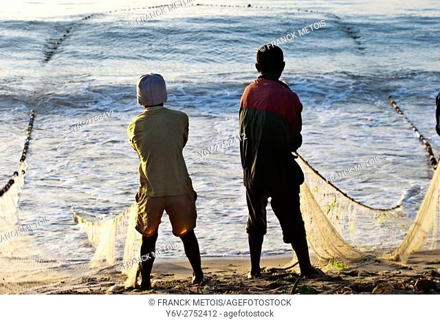 Boys are pulling a fishing net out of the water. At Toamasina ( Madagascar)