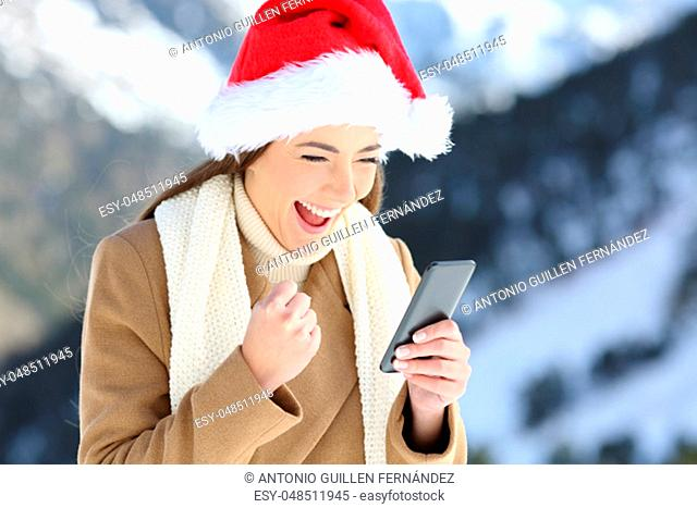 Excited woman reading on line news in christmas with a snowy mountain in the background