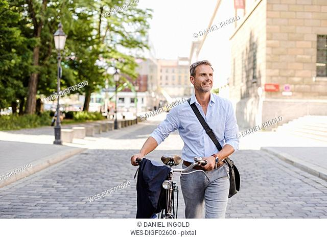Smiling man pushing bicycle in the city