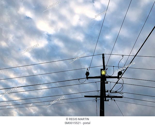 Power and telephone lines with a street light under a cloudy sky