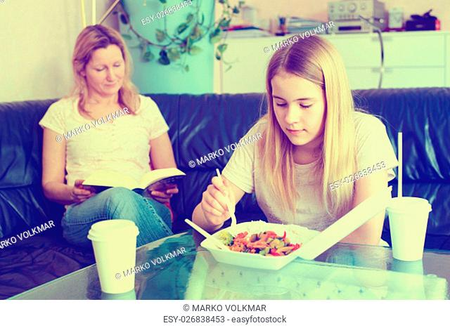mother reading a book and daughter eating fast food